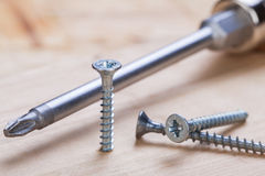 Phillips head screwdriver and wood screws. Close up view of a Phillips head screwdriver and threaded metal wood screws with one screw inserted into a plank of Royalty Free Stock Photos