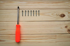 Phillips screwdriver and some screws on the new clean textured timber surface. Phillips screwdriver and row of several screws on the wooden planks surface Royalty Free Stock Image
