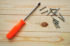 Phillips screwdriver and some screws on the wooden planks of pine timber Royalty Free Stock Image