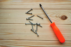 Phillips screwdriver and some screws on the wooden surface. Textured surface of new clean planks of spruce wood with phillips screwdriver and some screws on the Royalty Free Stock Image