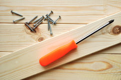 Phillips screwdriver with some screws on the wooden textured pine surface. New clean planks of pine wood and phillips screwdriver with some screws on the wooden royalty free stock photos