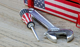 Phillips screwdriver with us flag printed and lock wrench. On wooden table royalty free stock photo