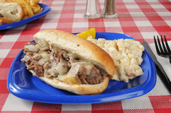 Philly cheese sandwich. A Philly cheese steak sandwich on a picnic table Stock Photos