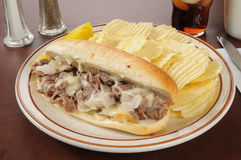 Philly cheese steak sandwich with chips. A Philly cheese steak sandwich with french fries and cola Royalty Free Stock Photo