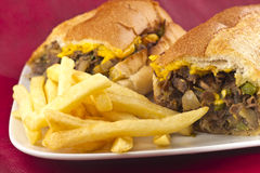 Philly Cheesesteak. A messy Philly Cheesesteak with onions peppers and mushrooms, fries on the side Stock Images