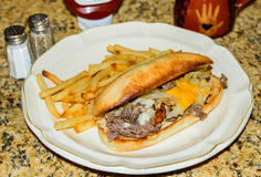 Philly cheesesteak sandwich and fries Stock Photos