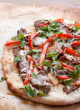 Philly steak pizza. A homemade philly steak pizza rests on browned parchment paper. The crust is golden brown, the steak is covered in melted cheese and has Royalty Free Stock Photography