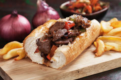 Philly steak sandwich. With french fries served on wooden board Stock Photo