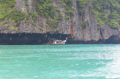 PhiPhi Ley Island. A small wooden boat under the cliffs of PhiPhi Ley Island in the Andaman Sea in Thailand Stock Images