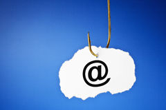 Phishing E-mail Concept. E-mail symbol printed on a piece of paper hooked on a fishing hook. Phishing and data protection concept Stock Photos