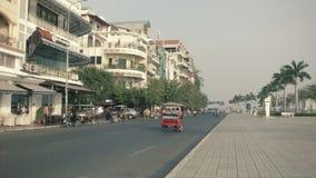 PHNOM PENH, CAMBODIA: Asian transport traffic on the central waterfront street with cars, motorbikes, tuk-tuks. Stock Photo