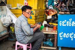 Phnom Penh, Cambodia - December 7, 2018. A street cobbler works on shoes. This street cobbler works on the footpath fixing shoes for anyone who needs work done stock photography