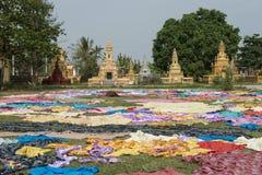 Phnom Sampeau Temple. Battambang, Cambodia. Golden pagodas of Phnom Temple Sampeau. Large colorful fabrics lying on the field. Battambang, Cambodia Royalty Free Stock Photos