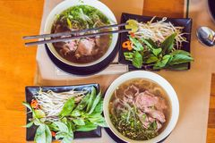 Pho Bo - Vietnamese fresh rice noodle soup with beef, herbs and stock photo