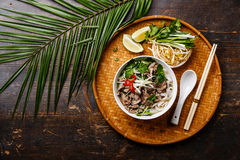 Pho Bo vietnamese Soup. With beef on bamboo tray and palm branch on wooden background royalty free stock photo