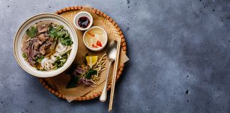 Pho Bo vietnamese Soup with beef in tray. On concrete background copy space royalty free stock image