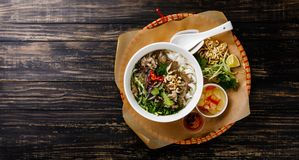 Pho Bo vietnamese Soup with beef in tray. On wooden background copy space royalty free stock photography