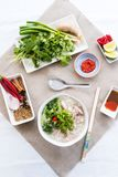 Pho ga soup with the serving sauces, herbs and spices Stock Photos