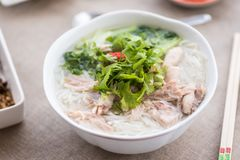 Pho ga soup with the serving sauces, herbs and spices Royalty Free Stock Photos