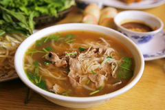 Pho Tai. A bowl of hot Pho Tai on a wood table stock photo