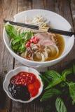 Pho Vietnamse在老木头的汤面 食物的图象做广告 库存照片