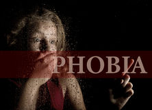 Phobia written on virtual screen. hand of frightened young girl melancholy and sad at the window in the rain. Stock Images