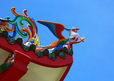 Phoenix statue on the roof of a Chinese temple under blue sky vi Stock Photos