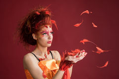 Phoenix. Young girl portrait and flying feathers. Woman holds a feather in hands. Royalty Free Stock Photos