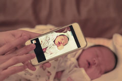 Η ασιατική μητέρα παίρνει μια φωτογραφία του θηλυκού γιου μωρών της με το έξυπνο phon Στοκ Φωτογραφίες