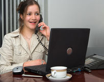 On the phone. Friendly secretary on the phone, with laptop Stock Photography