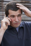 On the phone. Close up of worried man with mobile phone royalty free stock photos