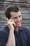 On the phone. Close up of smiling man outdoors with a mobile phone royalty free stock image