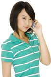 On The Phone. A young asian woman on the phone wearing green top on white background stock images