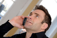 On the phone. Cute man talking on the phone being happy Royalty Free Stock Images