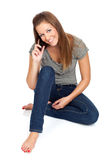 On the phone. Beautiful young woman talking on a mobile/cell phone, isolated on white Royalty Free Stock Photography