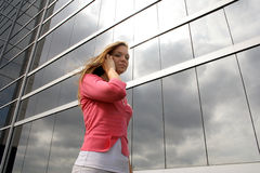 On a phone. Young woman in front of business building talking on a cell phone Royalty Free Stock Photo