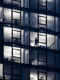 On the Phone. Sillouette of business man in skyscraper on the telephone - at night Stock Photography