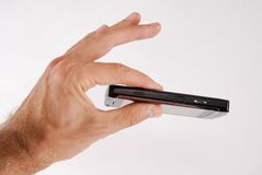 Phone 5. Glossy black cell phone in a man's hand Stock Images