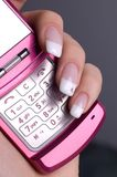 Phone. Young woman's hand holding a pink mobile phone Royalty Free Stock Photography