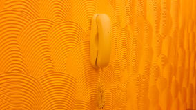 Phone on abstract wall design work. Wired phone, hanging on a yellow wall . The walls are made in exclusive version of the designer , in the  style of abstract Stock Photos