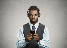 Phone addicted business man with headphones Royalty Free Stock Photo