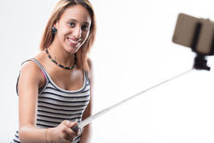 Phone addicted girl having fun with her beloved smartphone. Young woman using a selfie stick to make herself a photographic portrait with her smartphone smiling Stock Image