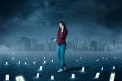 Phone addicted people, consciousness manipulation. Phone addicted people. Woman talking by smartphone, a lot of phones with glowing screens under her feet royalty free stock photography