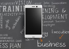 Phone against grey background with chalk written business training words. Digital composite of Phone against grey background with chalk written business training Royalty Free Stock Image