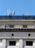Phone antennas on the roof. Two big phone antennas on the roof of an representative building, portrait cut Stock Images