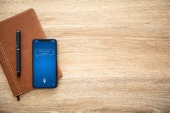 Phone with app personal assistant on screen and notebook. Phone with app personal assistant on screen and wooden table with a notebook royalty free stock images