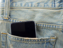 Phone in a back pocket of a denim jeans as a background. Pocket  jeans  background Phone  back Royalty Free Stock Images