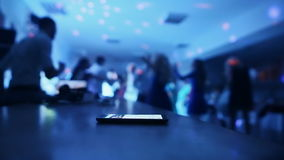 Phone on the background the dancing people at a party