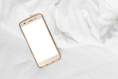 Phone on bed sheets Stock Photo