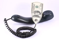 Phone Bill. Telephone receiver with 100 usd in extension of the cord Stock Image